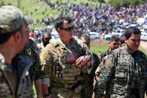 ضابط اميركي من قوات التحالف بقيادة اميركية يتحدث الى عناصر من وحدات حماية الشعب