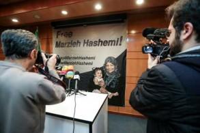 صحافيون يصوّرون ملصقًا تظهر فيه الصحافية التي تعمل لحساب قناة