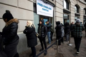 موظفون في الإدارات الفدرالية المتوقفة عن العمل أمام مطعم يوفر لهم طعاماً مجانياً في العاصمة واشنطن
