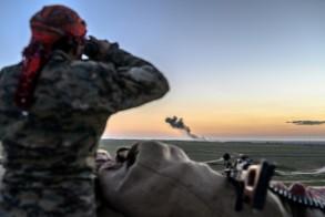 مقاتل من قوات سوريا الديموقراطية يستخدم منظارا لمراقبة جيب تنظيم داعش الأخير في بلدة الباغوز في شرق سوريا في 19 فبراير 2019