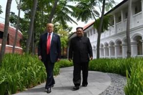 زعيم كوريا الشمالية كيم جونغ أون (يمين) يسير إلى جانب الرئيس الأميركي دونالد ترمب (يسار) خلال قمتهما التي جرت في سنغافورة بتاريخ 12 يونيو 2018