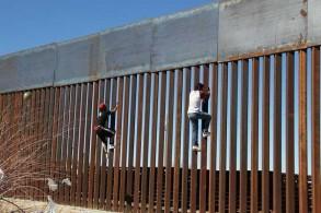 مهاجران يجتازان الحدود بين الولايات المتحدة والمكسيك