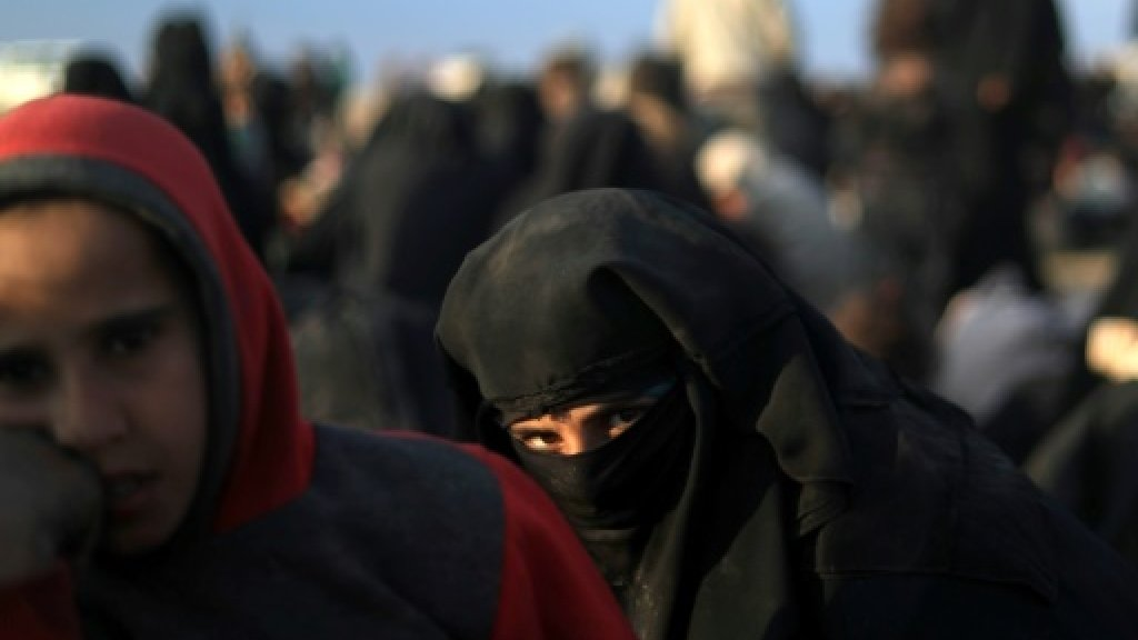 نسوة وأطفال ينتظرون في نقطة فرز بعد اجلائهم من بلدة الباغوز في شرق سوريا في 22 فبراير 2019 ا ف ب