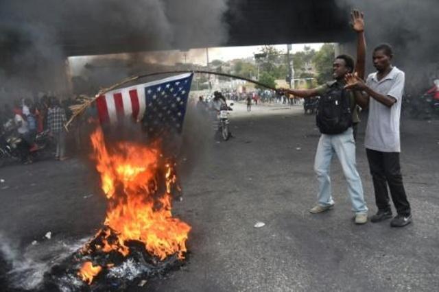 متظاهرون في هايتي يحرقون علم الولايات المتحدة في العاصمة بور او برنس في 15 شباط/فبراير 2019
