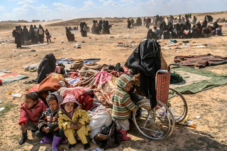 امرأة مصابة مع أطفالها الأربعة في عداد الخارجين من آخر جيب لتنظيم الدولة الإسلامية في شرق سوريا، في نقطة فرز تابعة لقوات سوريا الديموقراطية في محافظة دير الزور في 6 مارس 2019