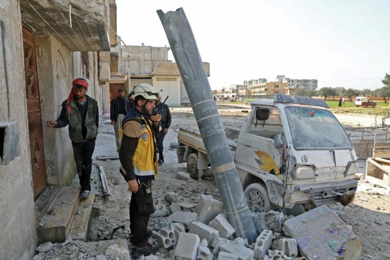 سوريون يقفون بجانب قذيفة صنعت في روسيا بعد قصف طال بلدة سرمين في إدلب بتاريخ 12 آذار/مارس 2019