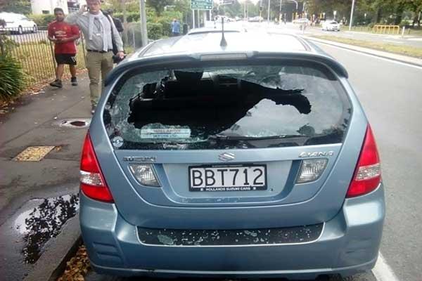 مارة قرب سيارة مكسورة النوافذ في موقع إطلاق النار على مسجد في مدينة كرايست تشيرش في 15 مارس 2019