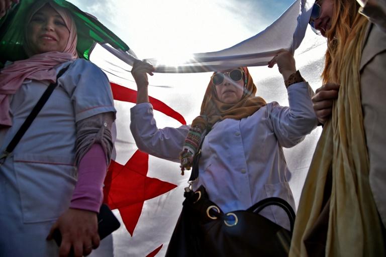 جزائريون يسيرون تحت علم جزائري عملاق أثناء تظاهرة للمدرسين والتلاميذ في العاصمة الجزائرية ضد تمديد ولاية الرئيس عبد العزيز بوتفليقة في 13 مارس 2019