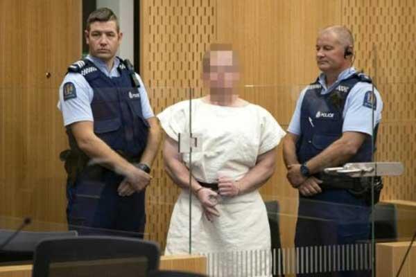 الأسترالي برينتون تارنت الذي ارتكب المجزرة في مسجدين في كرايست تشيرش في نيوزيلاندا يمثل أمام المحكمة في 16 مارس 2019 مشكلًا بإبهامه وسبابته شارة العنصريين من أتباع نظرية تفوق العرق الأبيض
