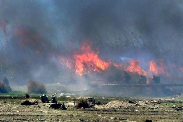 رجال يُشتبه أنهم من مقاتلي داعش يسيرون بين لهب النيران إثر قصف على جيبهم الأخير في بلدة الباغوز
