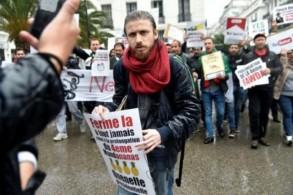 المصمم الجزائري زيري أولمان يعرض يافطاته خلال تظاهرة في الجزائر في 20 آذار/مارس 2019