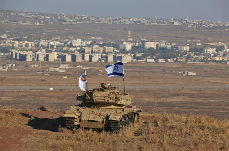 صورة من الارشيف التقطت في 18 تشرين الأول/أكتوبر تظهر علما اسرائيليا يرفرف فوق أنقاض دبابة اسرائيلية على تلة في القطاع الذي تحتله إسرائيل من مرتفعات الجولان