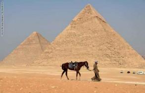 رجل مع حصانه يمر امام اهرامات الجيزة