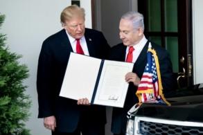 ترمب ونتانياهو الذي يمسك وثيقة اعتراف ترمب بسيادة إسرائيل على هضبة الجولان