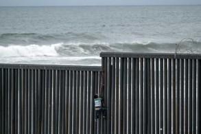 مهاجر من أميركا الوسطى يتسلق سياجًا حدوديًا للعبور من تيخوانا المكسيكية إلى سان دييغو الأميركية بتاريخ 21 مارس 2019