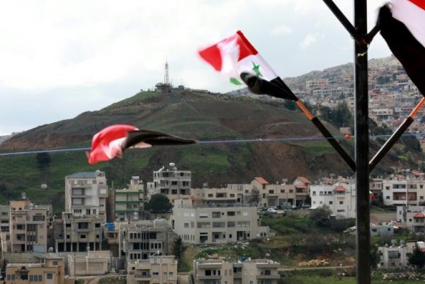 أعلام سورية مرفوعة في بلدة عين التينة المطلة على قرية مجدل شمس الواقعة في الجزء الذي تحتله إسرائيل من مرتفعات الجولان