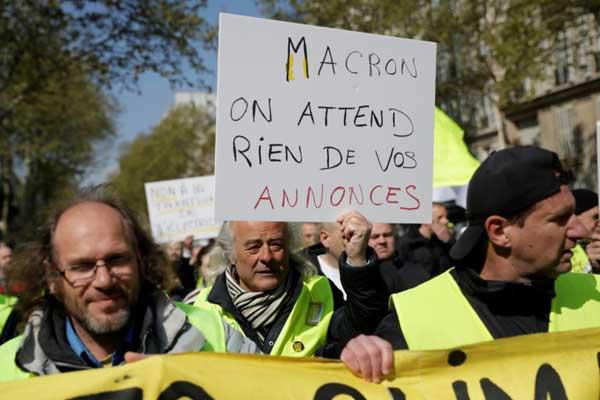 متظاهرون من السترات الصفراء يحملون لافتة كتب عليها