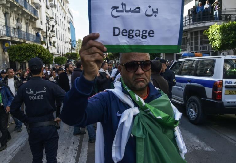 متظاهر يرفع لافتة تطالب برحيل الرئيس الانتقالي عبد القادر بن صالح في العاصمة الجزائرية في 10 نيسان/ابريل 2019