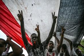 متظاهرون سودانيون يهتفون ويرفعون علامة النصر خلال تجمع خارج مقر القيادة العامة للجيش السوداني في الخرطوم بتاريخ 18 نيسان/ابريل 2019