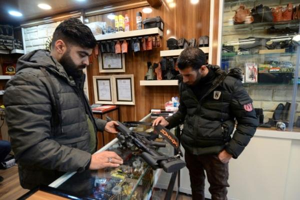 يتفقد بندقية في أحد محلات بيع الاسلحة في الموصل في 20 أبريل 2019
