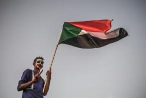 متظاهر سوداني يلوّح بعلم بلاده أمام مقرّ القيادة العامة للجيش في الخرطوم في 20 أبريل 2019