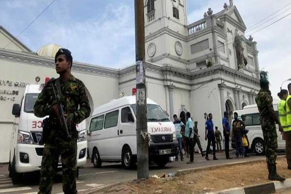 شرطي يقف أمام إحدى الكنائس التي طاولتها التفجيرات
