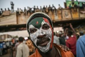 محتج سوداني رسم العلم السوداني على وجهه خلال احتجاج امام مقر الجيش في الخرطوم في 20 ابريل 2019