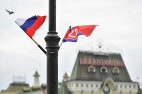 العلمان الكوري الشمالي والروسي على عمود كهرباء أمام محطة القطارات في فلاديفوستوك