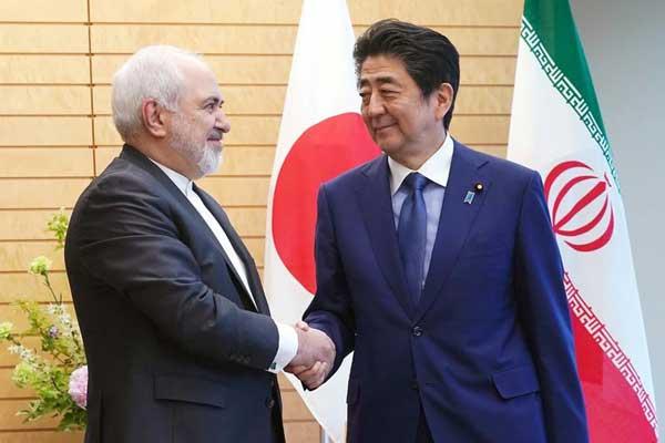 رئيس وزراء اليابان شينزو آبي يصافح وزير الخارجية الإيراني محمد جواد ظريف في طوكيو اليوم الخميس