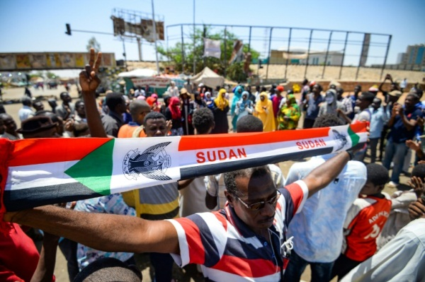 متظاهر سوداني يرفع يافطة أمام مقر الاعتصام في الخرطوم في 14 مايو 2019