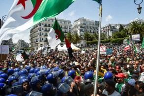 متظاهرون جزائريون يرفعون الأعلام الوطنية أمام مبنى البريد المركزي في العاصمة بتاريخ 17 مايو 2019