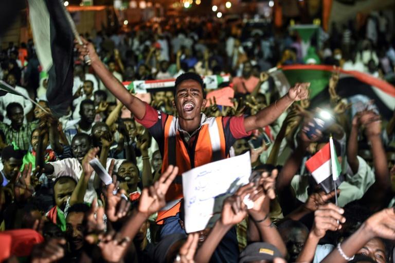 محتجون سودانيون يلوحون بالأعلام وشارات النصر خلال اعتصامهم أمام مقر الجيش في الخرطوم في 19 ايار/مايو 2019