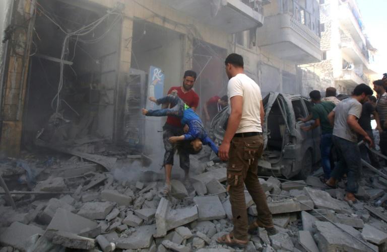 شاب يخرج طفل من بين الانقاض عقب قصف لقوات النظام وحلفائها على بلدة معرة النعمان في ادلب التي يسيطر الجهاديون في 26 أيار/مايو