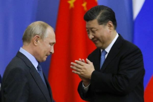 الرئيس الروسي فلاديمير بوتين (يسار) ونظيره الصيني خلال حفل تسليم شي جينبينغ شهادة من جامعة سان بطرسبورغ