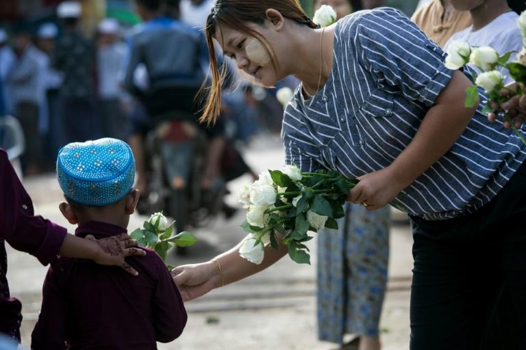 امرأة بوذية تقدم وردة بيضاء لطفل مسلم بعد أن أدى صلاة عيد الفطر في بلدة ثان لين على مشارف رانغون