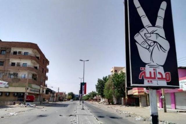 صورة التُقطت في 6 حزيران/يونيو 2019 يظهر فيها شارع فارغ في الخرطوم ولافتتان كتب على إحداها