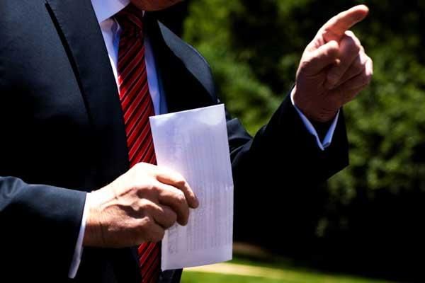 الرئيس الأميركي دونالد ترمب ملوّحًا بوثيقة اتفاقه حول الهجرة مع المكسيك في البيت الأبيض في 11 يونيو 2019