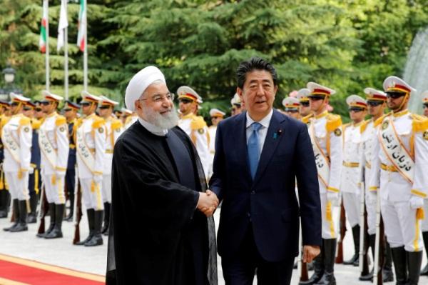 الرئيس الايراني حسن روحاني (يسار) مستقبلا رئيس الوزراء الياباني شينزو آبي في القصر الرئاسي في طهران