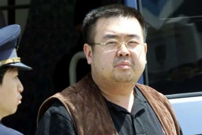 صورة التقطت في الرابع من مايو 2001 تظهر مسؤولًا في الهجرة يقتاد كيم جونغ نام إلى طائرة في مطار ناريتا قرب طوكيو