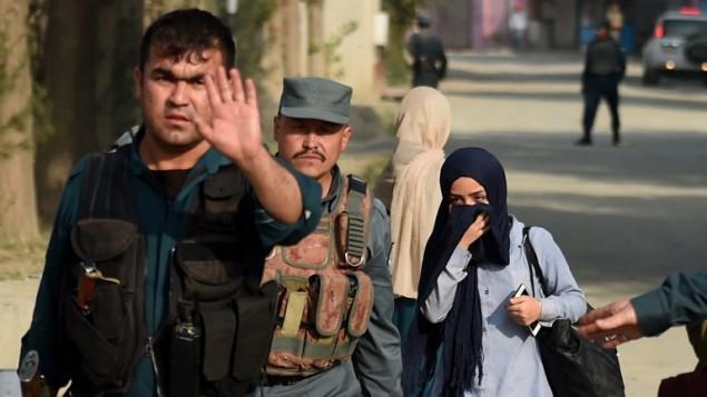 الشرطة الافغانية تواكب طالبة كانت عالقة داخل حرم الجامعة الامريكية في كابول بعد هجوم استمر 10 ساعات، 24 اغسطس 2016