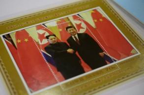 متجر في بيونغ يانغ يعرض طابعا بريديا تذكاريا يحمل صورة الزعيم الكوري الشمالي كيم جونغ أون (يسار) مصافحا الرئيس الصيني شي جينبينغ في 18 حزيران/يونيو 2019
