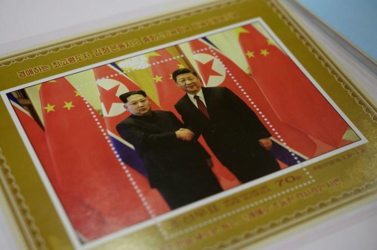 متجر في بيونغ يانغ يعرض طابعا بريديا تذكاريا يحمل صورة الزعيم الكوري الشمالي كيم جونغ أون (يسار) مصافحا الرئيس الصيني شي جينبينغ في 18 يونيو 2019