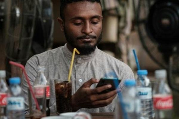 الشاب السوداني محمد عمر يتصل بالإنترنت على هاتفه النقال في أحد مقاهي الخرطوم