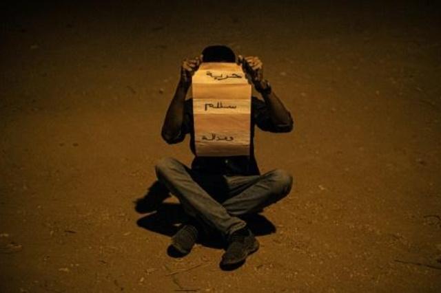 متظاهر سوداني يرفع شعارات الثورة
