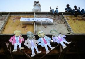 سودانيون فوق جسر يعلقون دمى ورقية تظهر وجوه عدة مسؤولين سابقين بينهم الرئيس الأسبق عمر البشير كتب فوقها