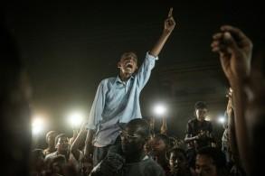 متظاهرون يرددون هتافات خلال تظاهرة ليلية على أضواء هواتفهم المحمولة، في الخرطوم في 19 حزيران/يونيو 2019