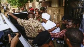 الرئيس السوداني المخلوع عمر البشير أثناء اقتياده إلى سجن كوبر، إثر مثوله أمام المحكمة بتهم فساد