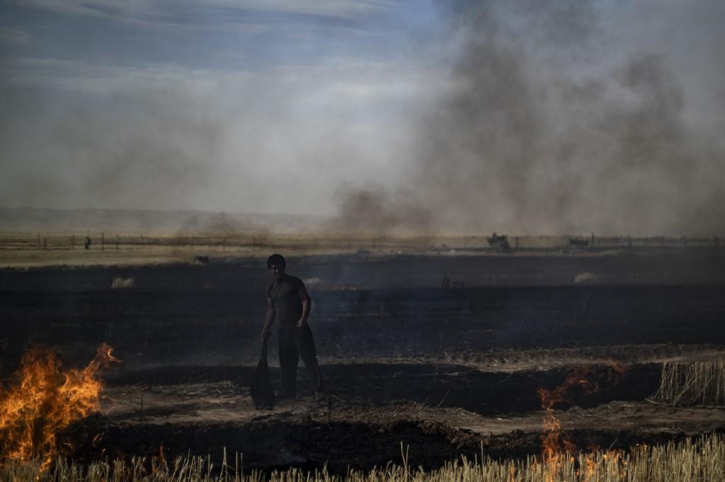 مزارع في شمال سوريا يحاول اطفاء نيران تلتهم حقلا للقمح