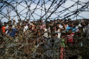 صورة التقطت من منطقة ماونغداو في ولاية راخين بتاريخ 25 نيسان/ابريل 2018 تظهر اللاجئين الروهينغا يتجمعون خلف سياج عند الحدود بين بورما وبنغلادش