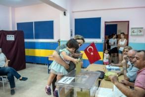امرأة تحمل طفلتها تدلي بصوتها في الانتخابات البلدية في اسطنبول في 23 يونيو 2019